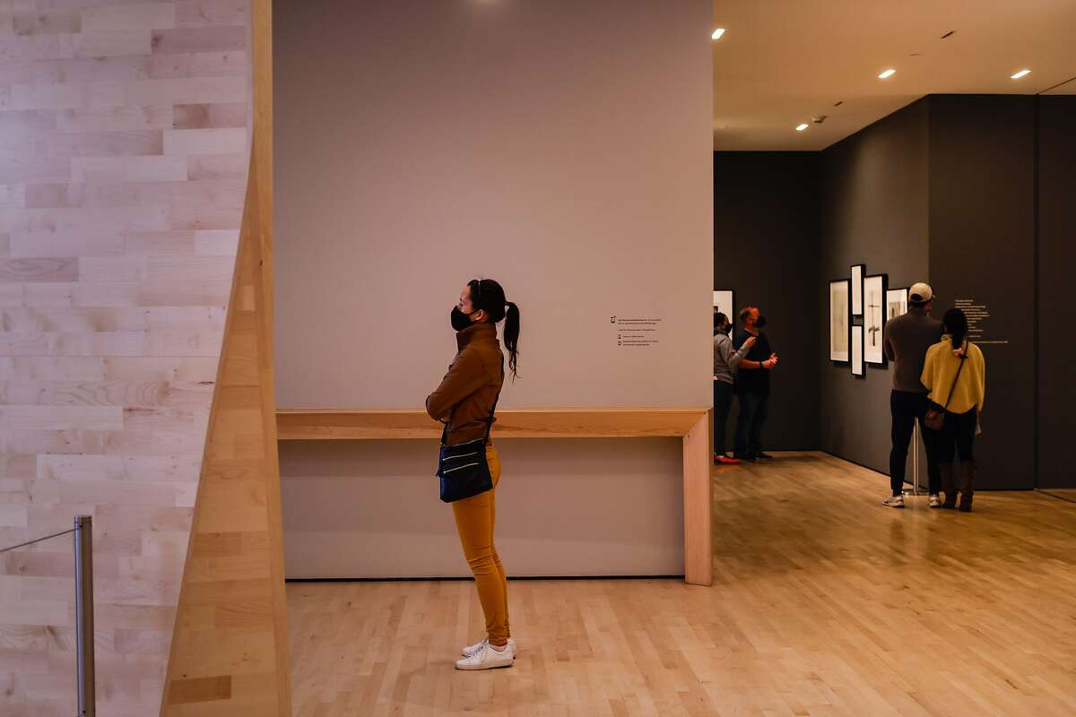 Paulnia Szyzdek watches a video at SFMOMA on its reopening day after nearly a year of being shuttered due to the pandemic.