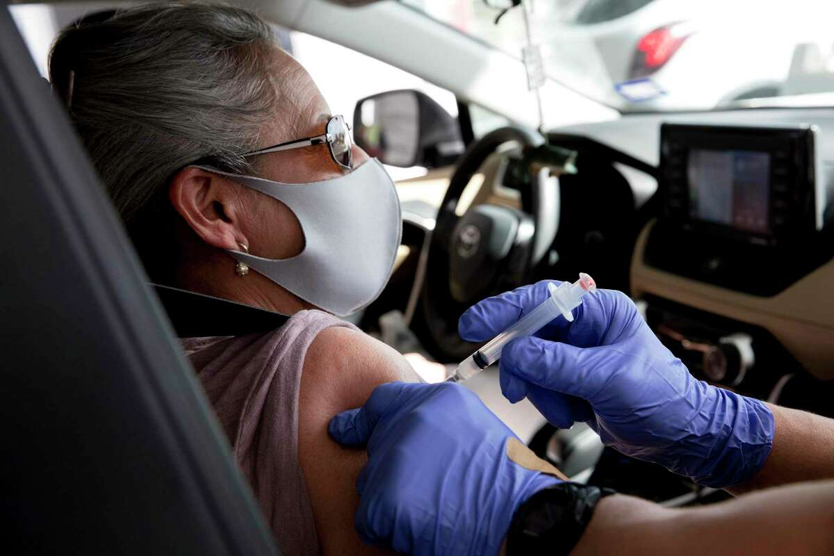 Mary Sanches, 69, receives his first dose of the Moderna COVID-19 vaccination Friday January 29, 2021 in a drive thru vaccination line at the Alamodome, organized by the San Antonio Fire Department.