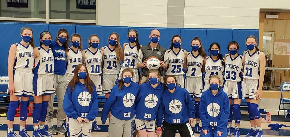 East Hampton girls basketball coach Shaun Russell poses with his varsity and JV players following his 400th career win last week.