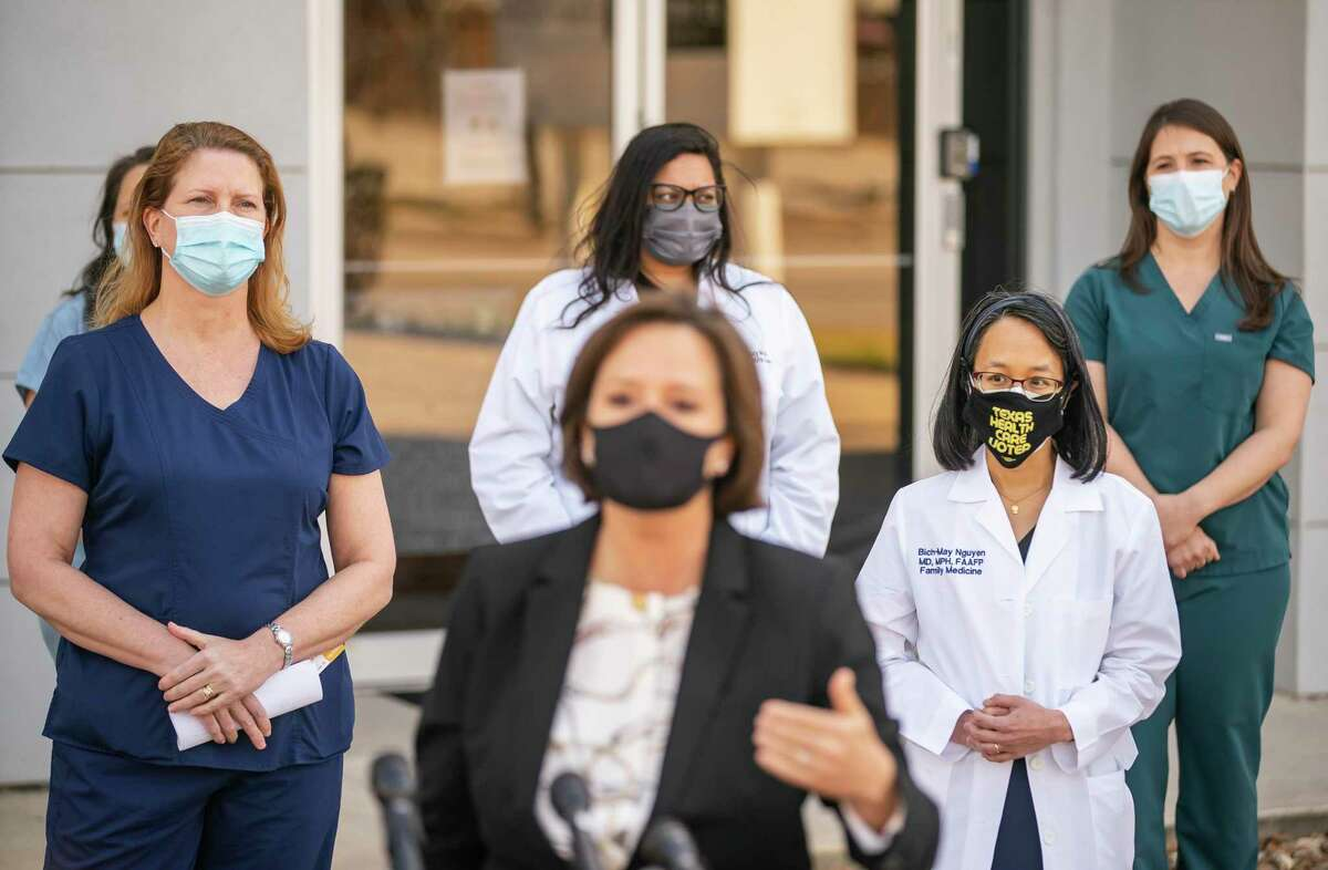 """Dr. Christina Propst (left) and Dr. Bich-May Nguyen (right) listen as State Representative Ann Johnson speaks to the media as local officials and medical professionals hold a press conference hoping to discourage the bar Concrete Cowboy from hosting a planned """"Mask Off Party"""" on this coming Wednesday, during an event for the media on Washington Avenue, Sunday, March 7, 2021, in Houston."""