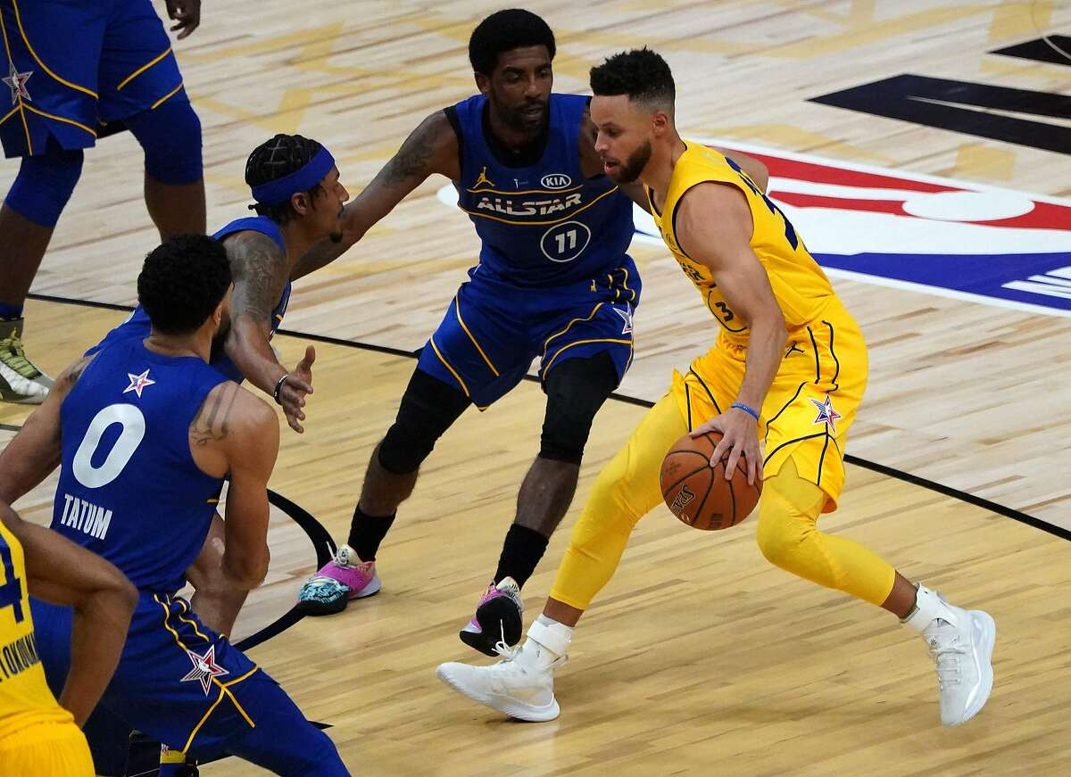 Stephen Curry (R) of Team LeBron James is defended by Kyrie Irving (C) of Team Duncan during the 70th NBA All-Star Game against team LeBron James at State Farm Arena in Atlanta, Georgia on March 7, 2021.