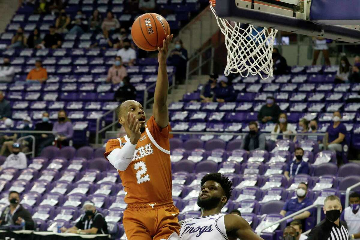 Texas guard Matt Coleman III (2) shoots over TCU guard Mike Miles (1) during the first half of an NCAA college basketball game in Fort Worth, Texas, Sunday, March 7, 2021. (AP Photo/Michael Ainsworth)
