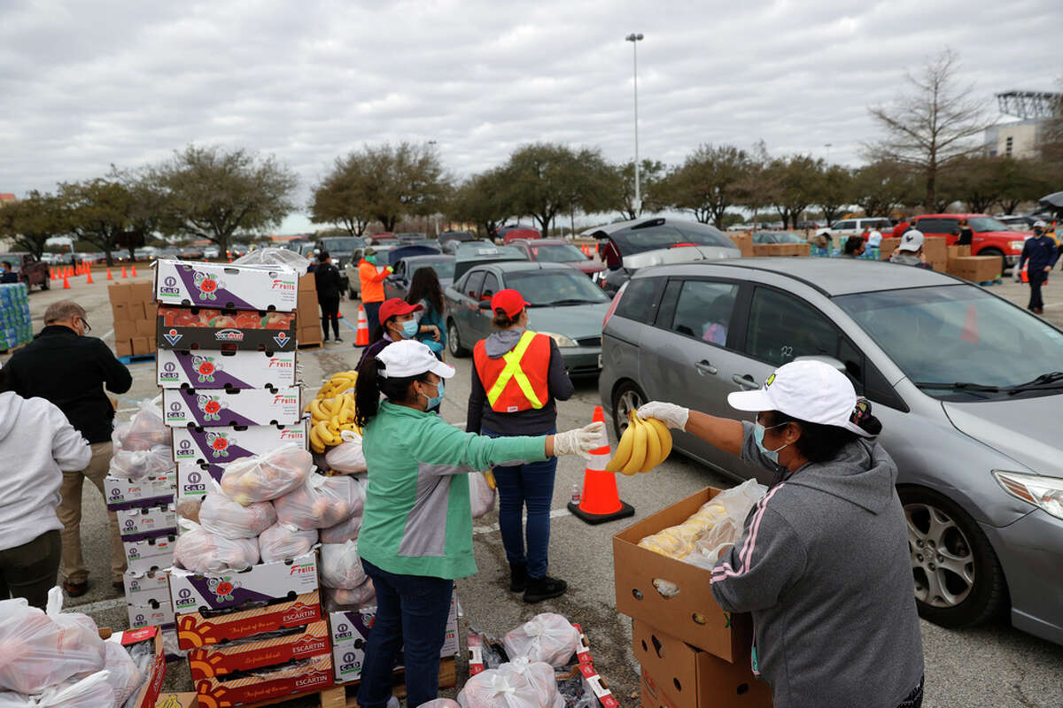 HOUSTON, TEXAS - FEBRUARY 21: Volunteers prepare to load food into cars during the Houston Food Bank food distribution at NRG Stadium on February 21, 2021 in Houston, Texas. Thousands of people lined up to receive food and water at a mass distribution site for Houston residents who are still without running water and electricity following winter storm Uri. The storm swept across 26 states with a mix of freezing temperatures and precipitation, knocking out power to millions across the state.