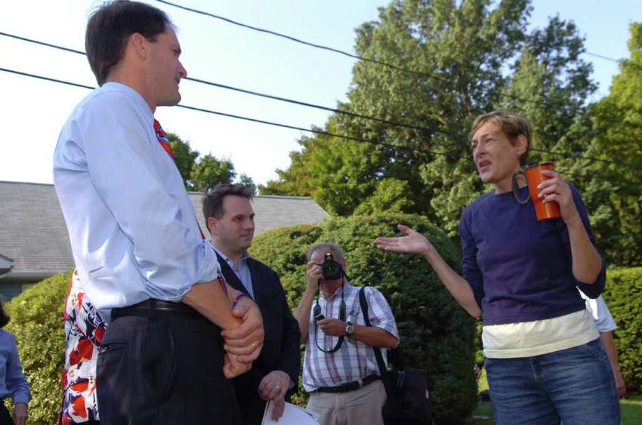 U.S. Rep. Jim Himes, D-Conn., left, and Drew Marzullo, Greenwich selectman, listen to homeowner Jody Stein Hawreluk, speak about  Byram River flooding on Monica Street, on Wednesday, Sept. 8, 2010. Photo: Helen Neafsey / Greenwich Time
