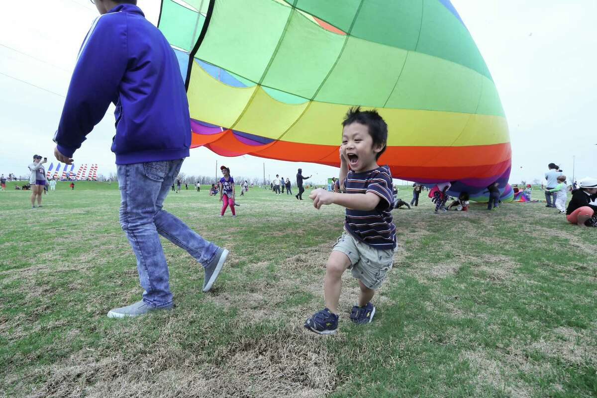 A youth runs from a large kite during the Cultural Kite Festival Saturday, March 3, 2018, in Sugar Land. The festival is a free event for all to see vibrant kites ride the wind and decorate the sky. The annual event was held at the Brazos River Park / Crown Festival Park at Sugar Land included a 24-foot rock wall, spring-free trampoline, face painting, henna tattoos, community booths, food trucks, stilt walkers and a main stage will come to life with cultural performances from local area groups. Awards were given for largest kite, smallest kite, most unusual/unique kite and the highest flying kite. ( Steve Gonzales / Houston Chronicle )