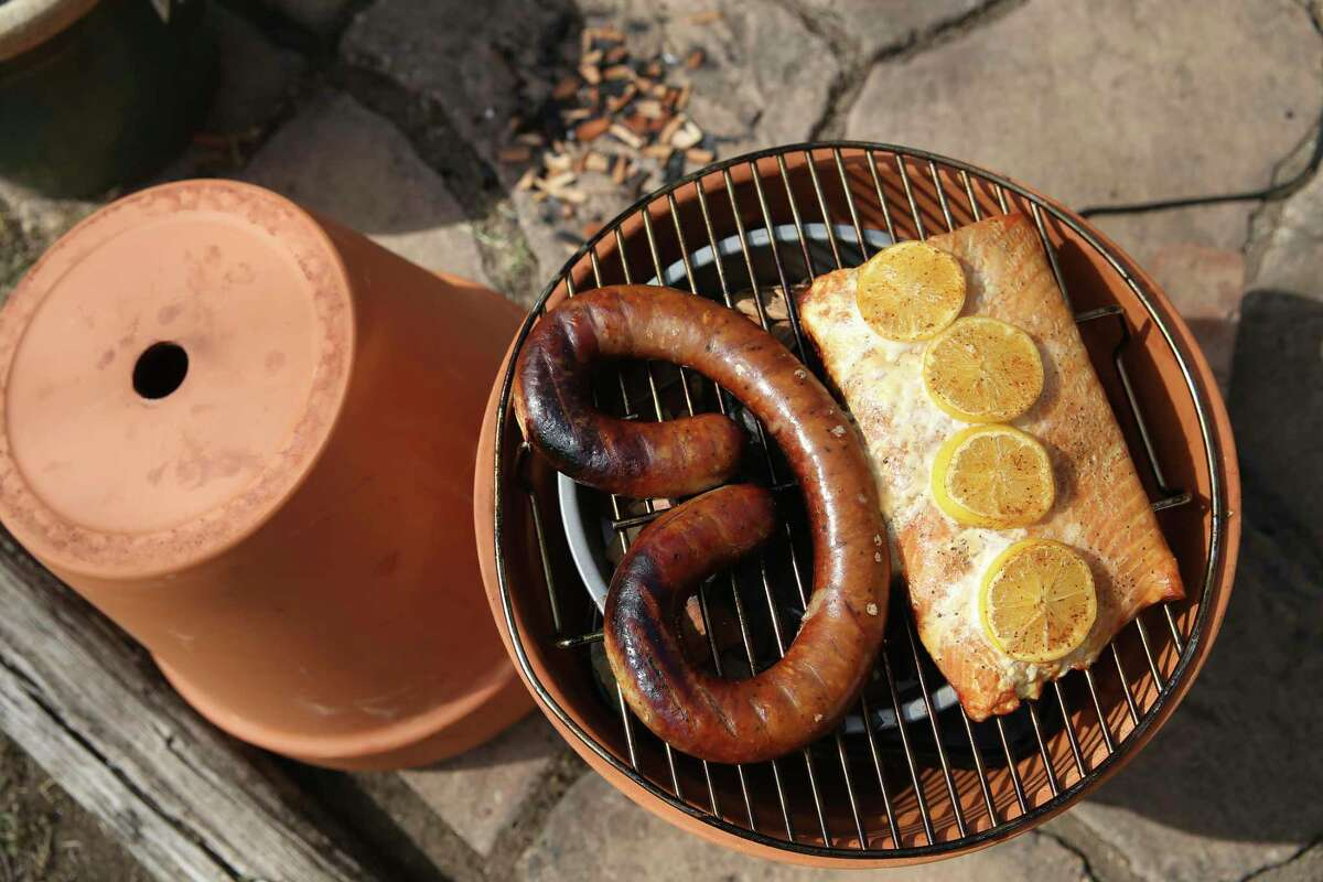 Finished smoked sausage and salmon that was cooked entirely inside a pair of flower pots with wood chips and an electric hot plate.