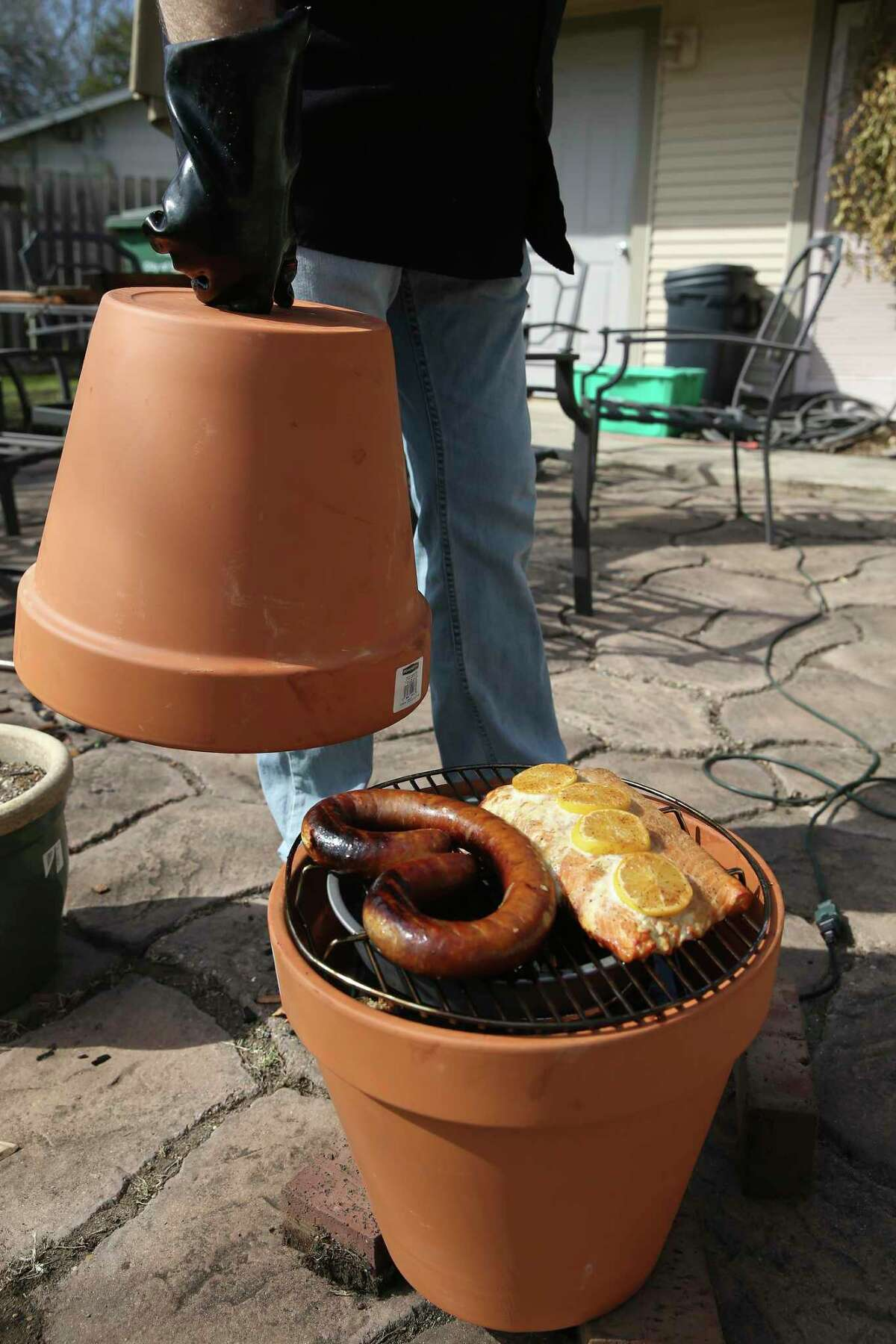 Chuck Blount smokes salmon and sausage in a rigged-up flower pot smoker.