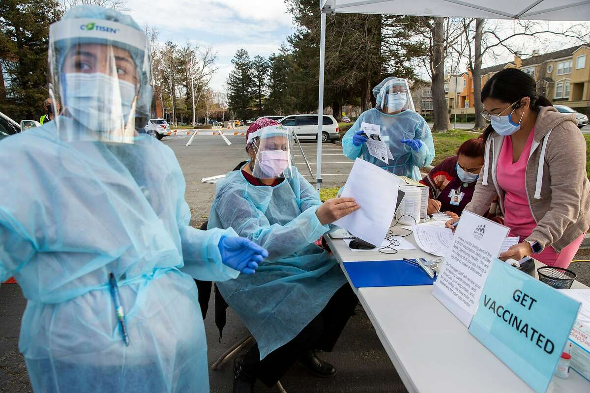 From left: Health workers Claudia Alegre, Liz Haley, Monica Towle, Rajinder Kaur and Yanette Sanchez work non-stop at the Bay Area Community Health to give the COVID-19 vaccine to a long line of cars at a drive-thru and walk-in station, Thursday, Jan. 21, 2021, in Fremont, Calif.
