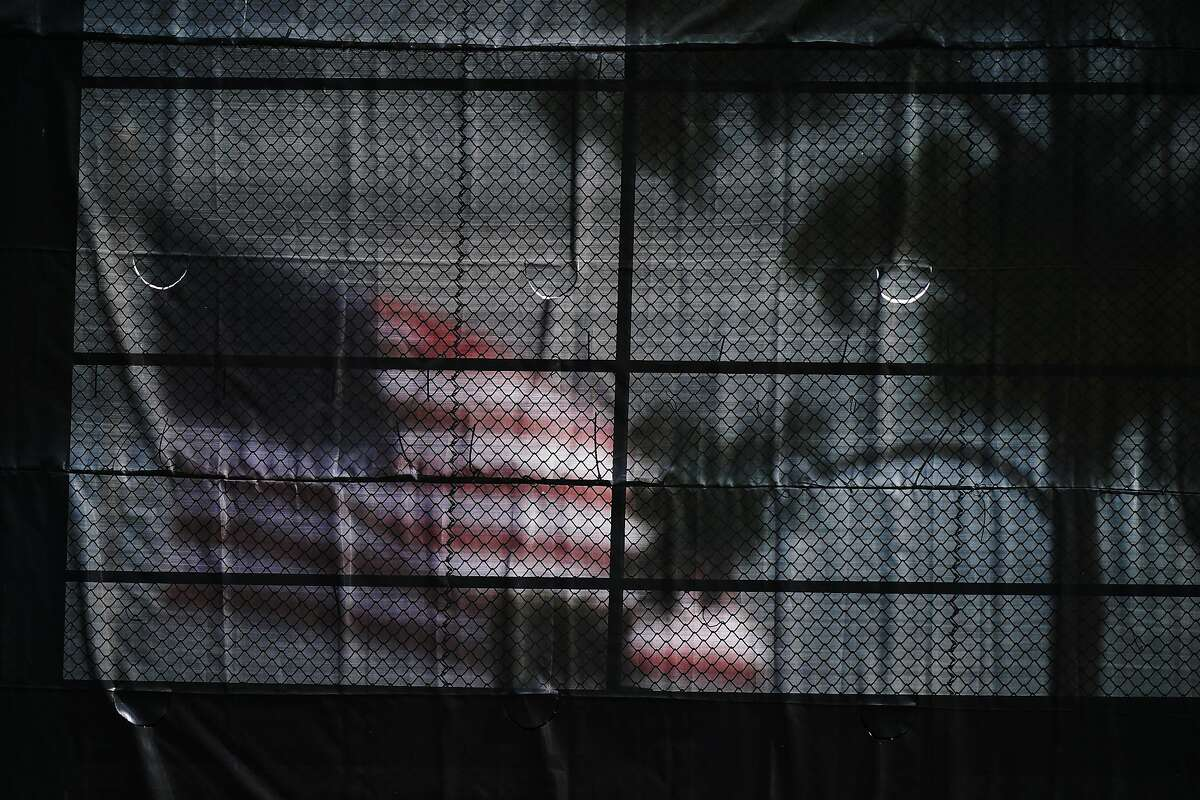 An American flag is seen through a baseball net during a spring training baseball game with the Pittsburgh Pirates and the Tampa Bay Rays on March 3, 2021, in Port Charlotte, Fla.