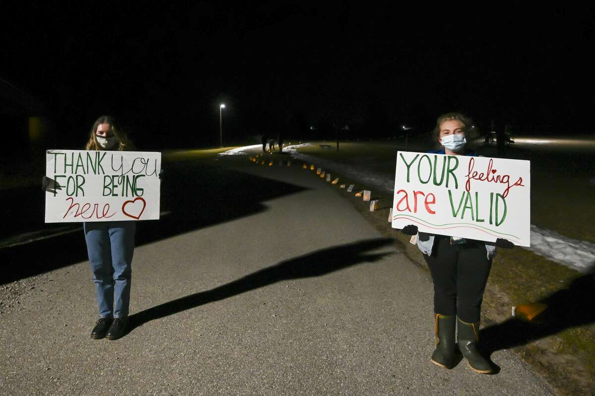 Midland High School students Jocelyn Stopka, left, and Emmy Mackenzie, right, hold up signs during a luminary walk organized by MHS students as the culmination of their