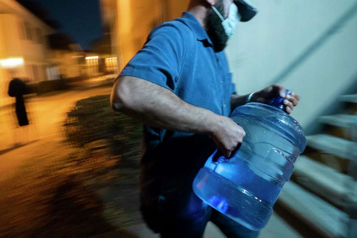 Haitham Nash fills up water bottles from a spigot outside a building in his apartment complex to use inside the apartment he shares with his parents, Sunday, March 7, 2021, at the Villas Del Paseo in Houston. Like so many in the complex, Nash hasn't had working water in his apartment since February's freeze. He finds himself filling up water bottles multiple times a day before and after work. Some days the spigots don't work. Then Nash has to go to a different complex to get water.