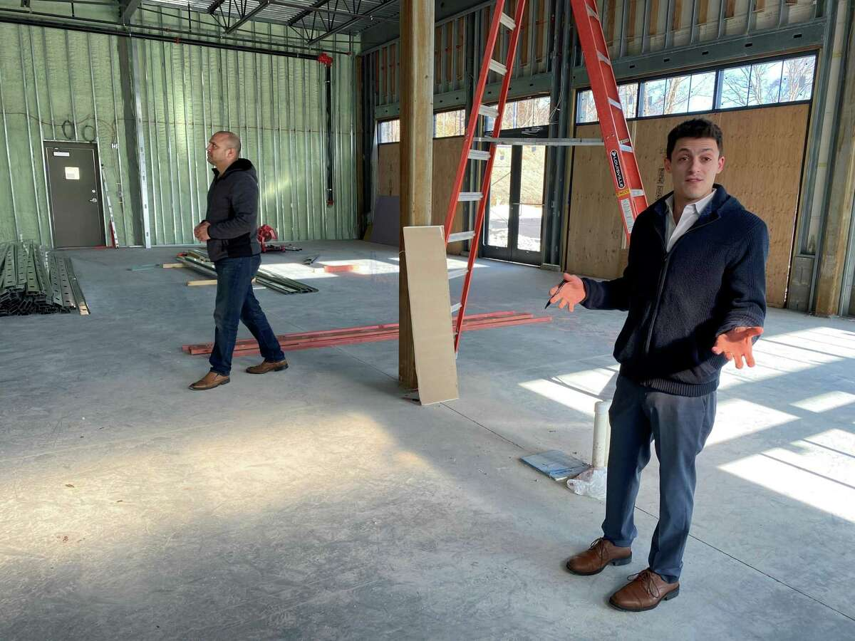 Joe Worthington describes the custom bar that will be the centerpiece of the new Ecco restaurant while Dan Camporeale inspects the framing on Thursday, March 4.