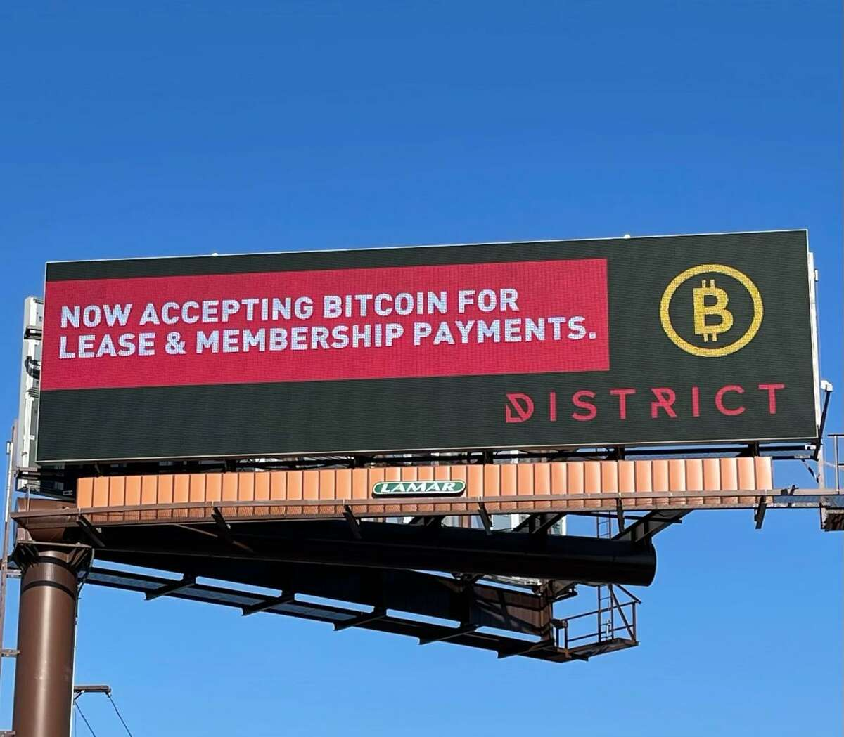 A billboard announcing that The District, a New Haven-based technology business incubator and co-working center, has begun accepting cryptocurrency as payment for membership fees and leasing costs.