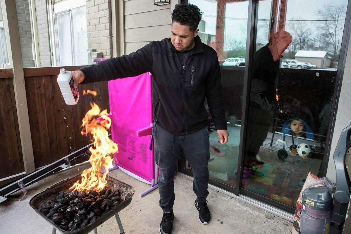 Kevin Morazan lights his charcoal grill to cook after losing power in the Greenspoint area due to rolling blackouts following an overnight snowfall Monday, Feb. 15, 2021 in Houston. Temperatures plunged into the teens Monday with light snow and freezing rain. The stove in his apartment is electric.