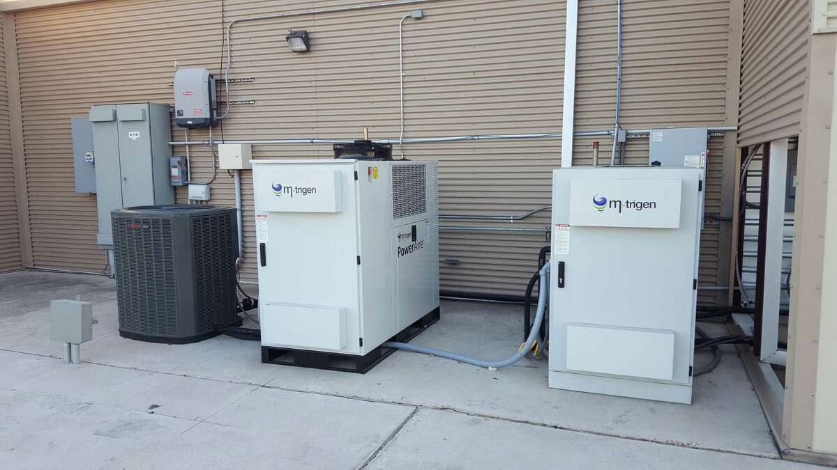 Two M-Trigen PowerAire units installed next to air conditioning compressors. M-Trigen units can provide power, air conditioning and heat during blackouts by relying on natural gas or propane. The Houston-based start-up is ramping production at it's local factory.