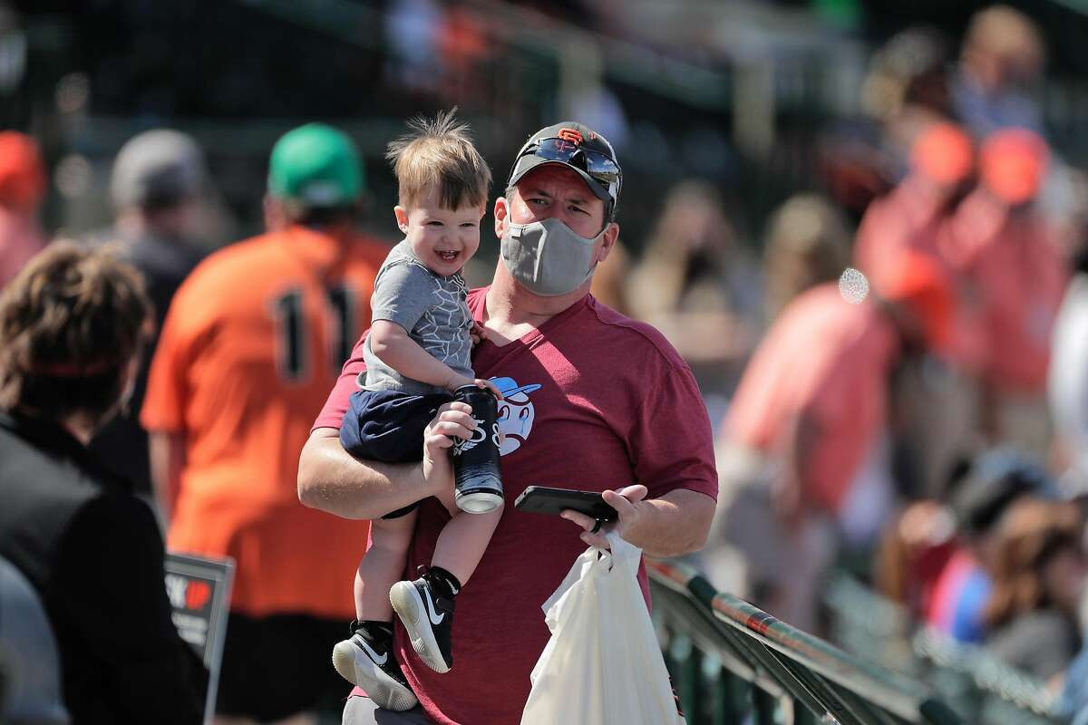 A fan carries his son through the concourse after stopping for refreshements as the San Francisco Giants played the Chicago White Sox in a spring training game at Scottsdale Stadium in Scottsdale, Ariz., on Thursday, March 4, 2021.