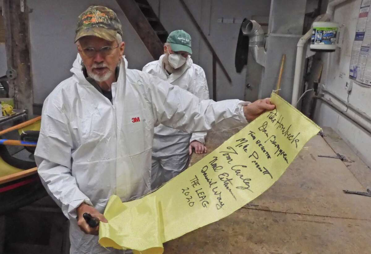 Peter Hornbeck of Hornbeck Boats holds up the piece of fabric signed by members of the LEAG who contributed to the building of a one-of-a-kind Hornbeck boat, which will be raffled by the Adirondack Center for Loon Conservation. The fabric was installed into the boat's hull.