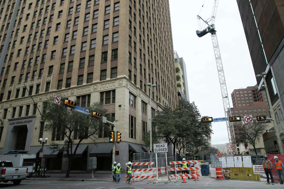A construction crane looms over East Commerce Street near the Drury Plaza Hotel San Antonio Riverwalk Work. The hotel's owner obtained a temporary restraining order preventing the crane from trespassing on the building's airspace.