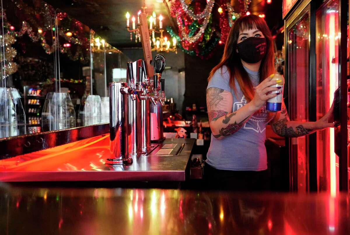 Lindsay Beale, general manager, prepares to open at Grand Prize Bar, 1010 Banks St., Monday, March 8, 2021 in Houston. A partition lines the bar among the Christmas decorations they decided to keep displayed. Small and medium-sized business owners in Houston said they strongly support vaccinations to protect against COVID-19 and plan to encourage their employees to get the shots, according to a survey of small business owners. Grand Prize Bar is one of the businesses that will be encouraging its staff to get vaccinated.