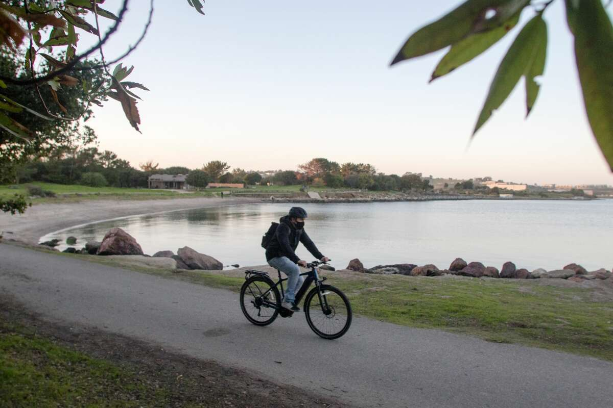 A bicyclist rides a path at Candlestick Point State Recreation Area near the ninth most polluted beach in California.