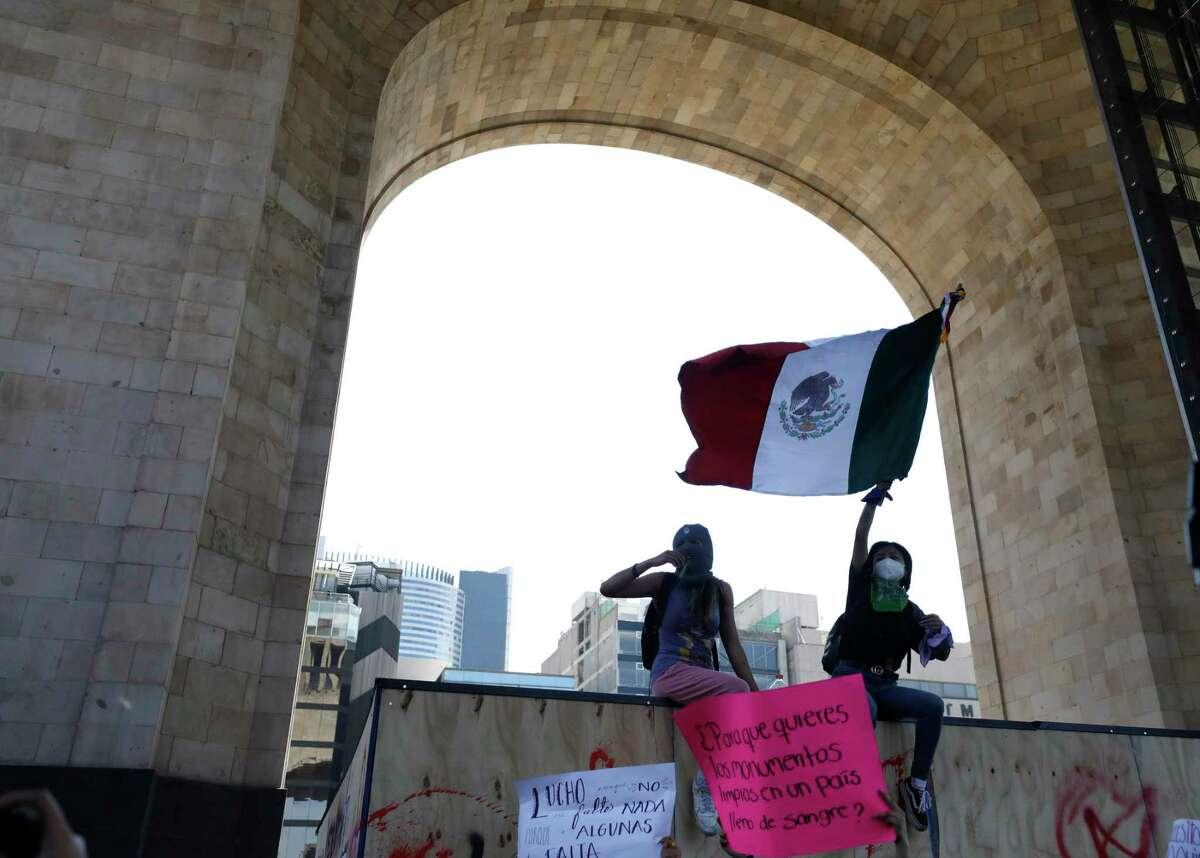 Mujeres ondean una bandera mexicana mientras se sientan en una pared de madera que protege el Monumento a la Revolución de México durante una marcha para conmemorar el Día Internacional de la Mujer y protestar contra la violencia de género, en la Ciudad de México, el lunes 8 de marzo de 2021.