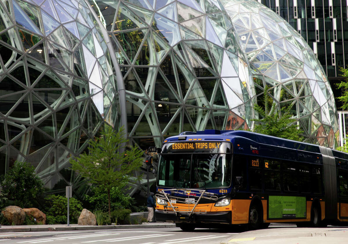 A King County Metro bus for essential trips only passes by The Spheres at the Amazon campus on April 30, 2020 in Seattle, Washington. Amazon recorded sales of $75.4 billion in the first three months of the year as many consumers increased their online purchases, up 26% over last year, but with net income for the same period falling nearly 31% due to costs of managing the coronavirus pandemic.