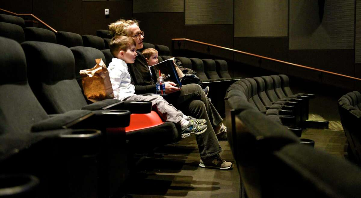 Leah Wiener, of Ridgefield, and her sons Max, 5, and Owen, 3, wait for a movie to start at the Prospector Theater. Friday, March 24, 2017, in Ridgefield, Conn.