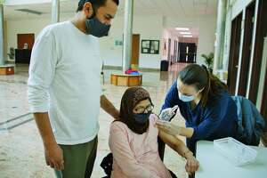 """Ali Haroon, left, stands by his mom, Amina Haroon, as she eceives her first dose of the Moderna Covid-19 vaccination, given by Laura Ordway, the public health pharmacist at The Collaboratory, Albany College of Pharmacy and Health Sciences. The Albany College of Pharmacy and Health Sciences held at vaccination clinic at the Al-Hidaya Center for people 65 years of age or older on Tuesday, March 9, 2021, in Latham, N.Y. The college had 50 doses they administered during the clinic. Stacy Pettigrew, assistant professor in the Department of Population Health Sciences at the college, said that the college has been holding small clinics like this one as a community outreach program to get people vaccinated who might have trouble signing up for vaccinations. Ahsan Memon, president of the board of directors for the mosque, said that when leaders of the mosque reached out to their members 65 years of age or older, some who were skeptical of getting the vaccine felt safer and signed up when they found out they would be getting it at the mosque. """"They felt reassured receiving the vaccination at the place where they are connected to God"""" Memon said.      (Paul Buckowski/Times Union)"""