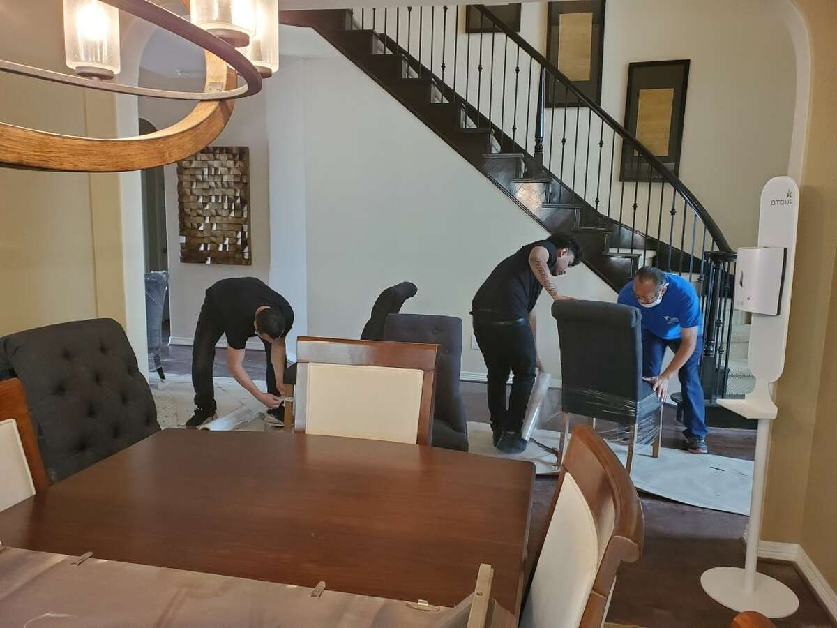 Movers from Vita Living and Fort Bend Women's Center collect donated furniture from Newmark Homes' model home. The home is being sold and the furniture will be put to use by the agencies in their living facilities.