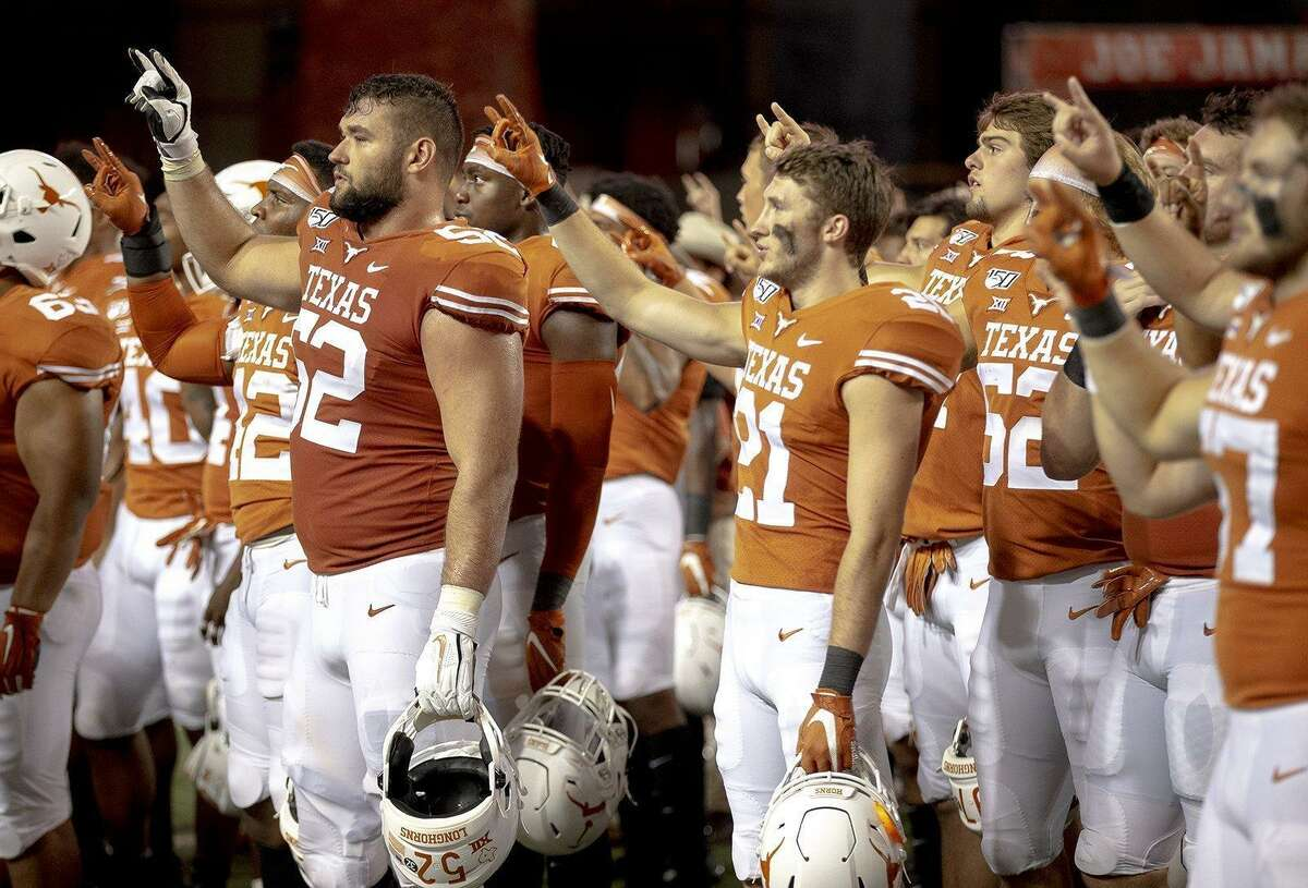 """Texas players stand for the playing of """"The Eyes of Texas."""" (Nick Wagner/Austin American-Statesman/TNS)"""