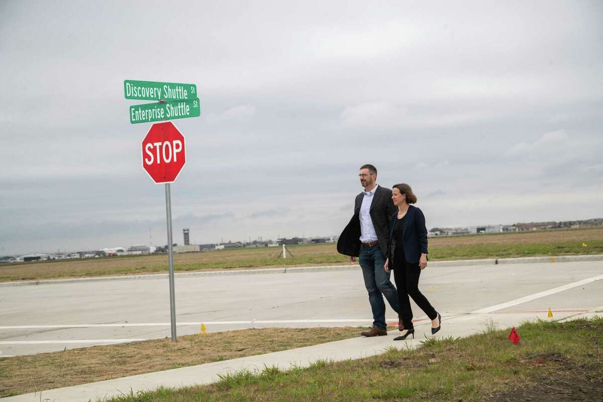 """Sarah """"Sassie"""" Duggleby, Venus Aerospace co-founder and CEO, and her husband Andrew Duggleby, Venus Aerospace co-founder and Chief Technology Officer walk the Discovery Shuttle Street and Enterprise Shuttle Street corner for a portrait in the Houston Spaceport where Venus Aerospace is looking to one day build its headquarters, Friday, March 5, 2021, in Houston."""