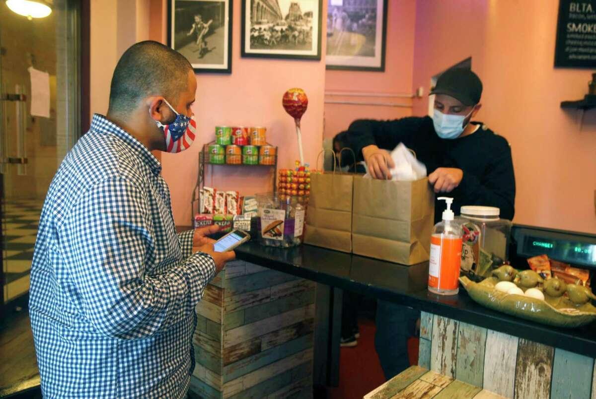 DoorDash driver Ali Badani (left) waits as Hamel Belayadi packs an order for delivery at Cafe Encore in in San Francisco.