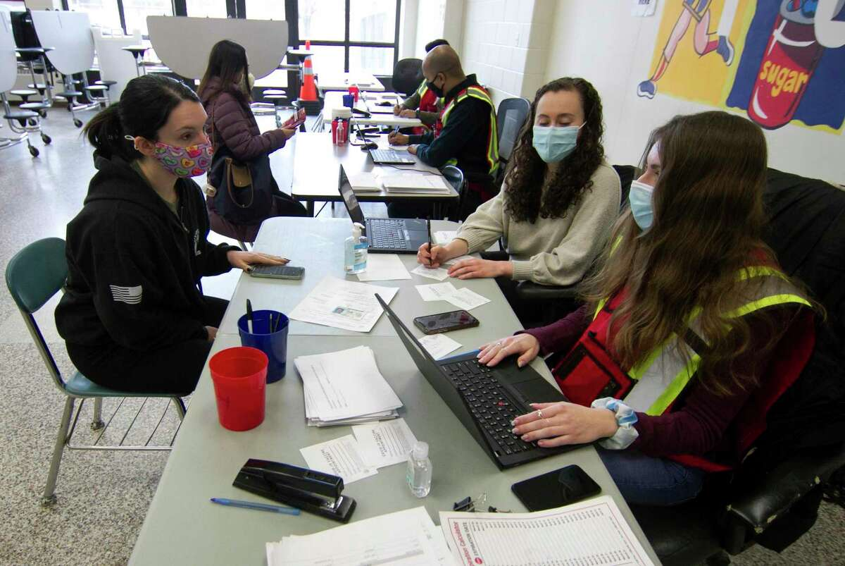 Danbury teacher Lauren Brown, left, checks in with staff to receive her Moderna COVID-19 vaccination at a clinic set up at Rogers Park Middle School in Danbury, Conn., on Saturday Mar. 6, 2021. Over 900 teachers and staff received the Moderna vaccine during the two-day clinic.