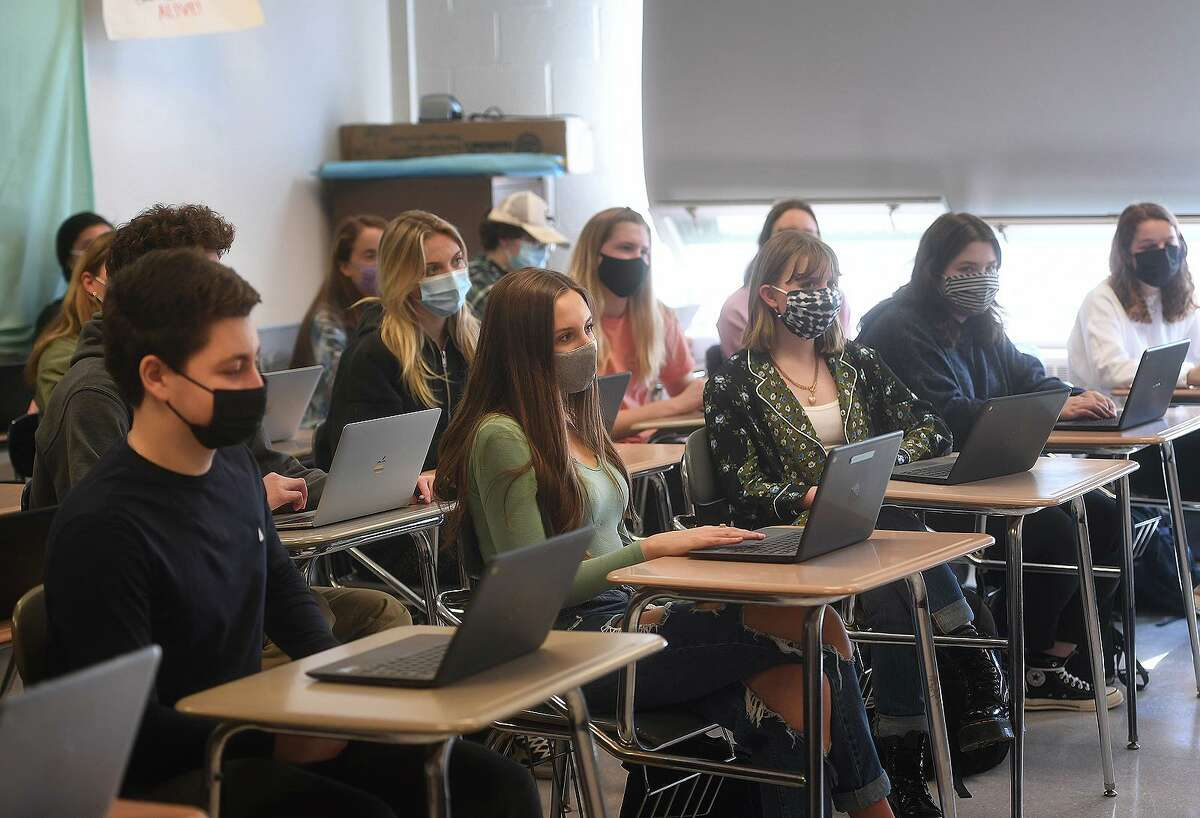 American studies students enjoy a return to a full classroom for the first time in a year at Ludlowe High School in Fairfield, Conn. on Tuesday, March 9, 2021.