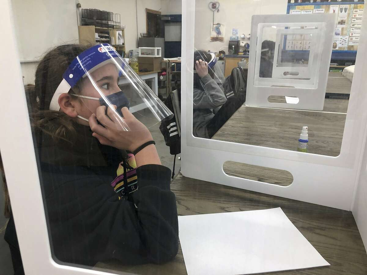 Students wearing face masks and face shields to protect from the coronavirus sit at their desks during class at the Sinaloa Middle School in Novato on March 2, 2021.