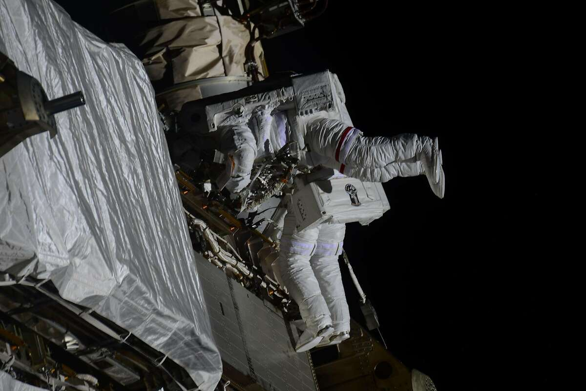 Kate Rubins (foreground) and Victor Glover install solar array modification kits on the space station Feb. 28.