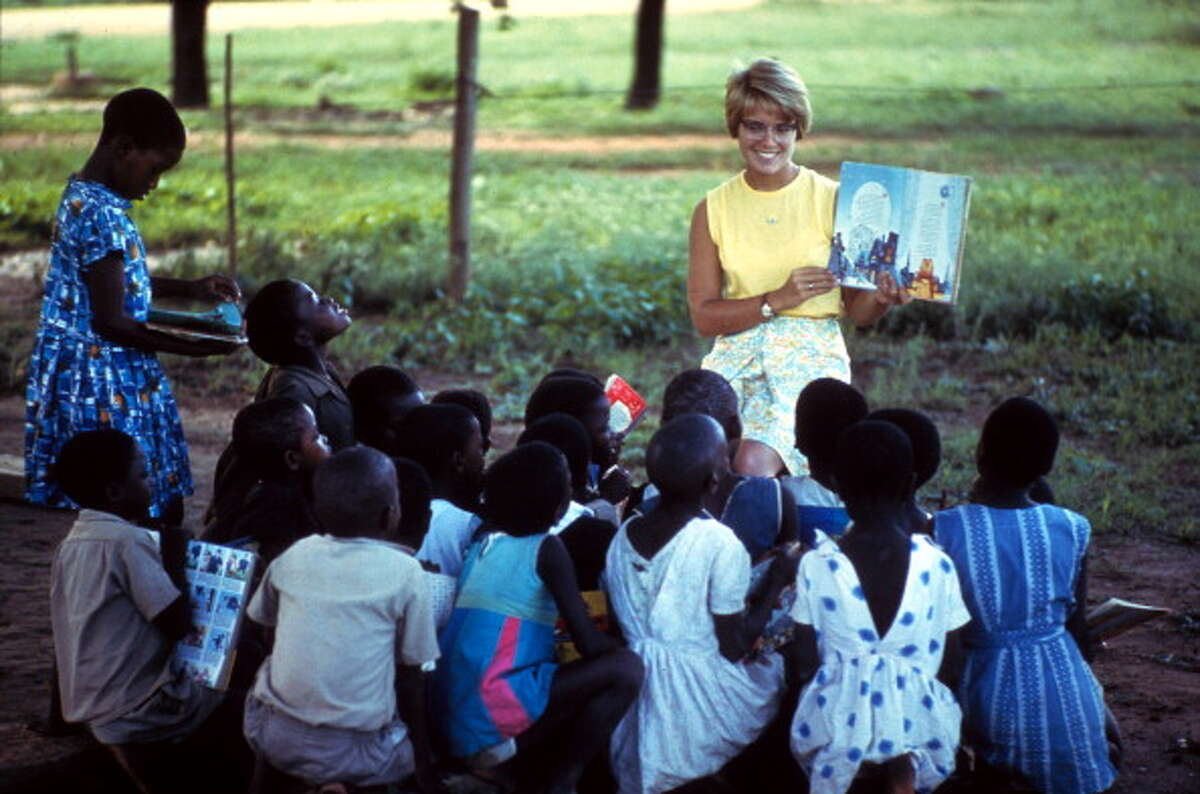 A Peace Corps volunteer teacher reads a children's book to the young students gathered around her, Botswana, 1960s.