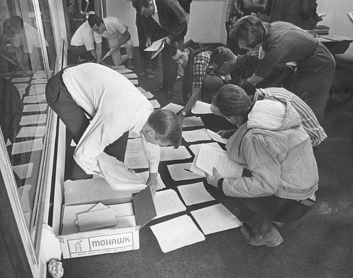 Peace Corps returnees pick up reports that they had to study during the seminar. After completing the seminar, they will work as instructors for other Peace Corps volunteers; 1966.