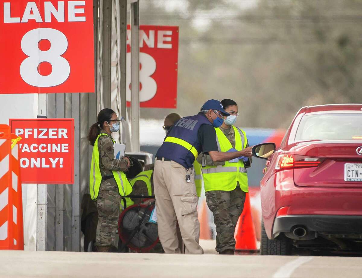 Military personnel help facilitate the administration of a vaccine to prevent COVID-19 at the FEMA-run mass vaccination site at NRG Park on Monday, March 8, 2021, in Houston.