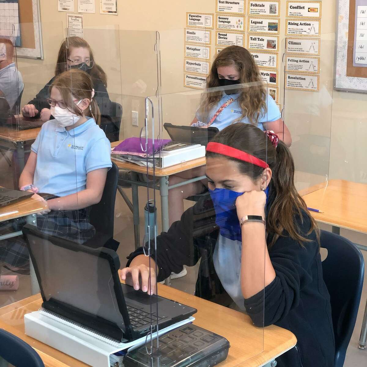Students from Epiphany Catholic School do their school work behind dividers. The Archdiocese of Galveston-Houston announced Monday, March 5, 2021 that all Catholic School students must continue to wear masks through the end of the school year.