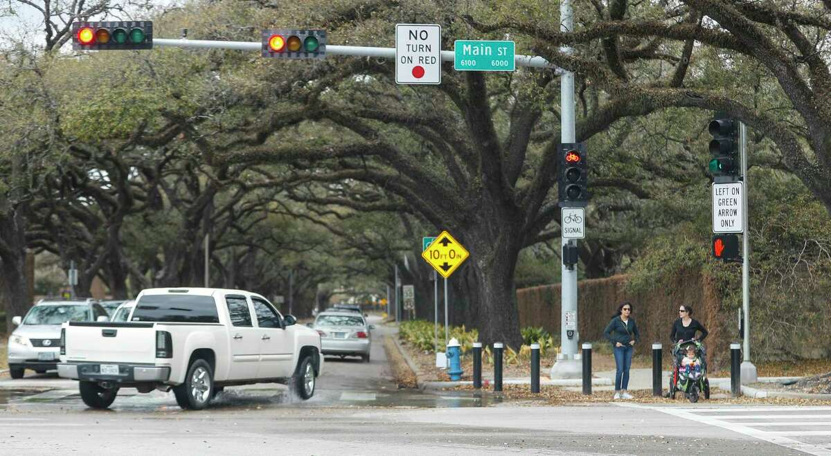 Women wait to cross Main Street at Sunset Boulevard on March 9, 2021, in Houston. Smart Growth America, a national advocacy group, said in its Dangerous By Design report that Texas went from 8th to 10th and Houston went from 23rd to 18th in terms of pedestrian risk.