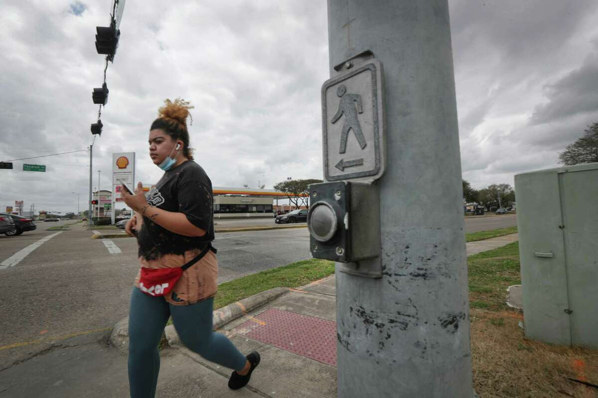 A woman uses the crosswalk at the intersection of Fondren and West Bellfort on March 9, 2021, in Houston.
