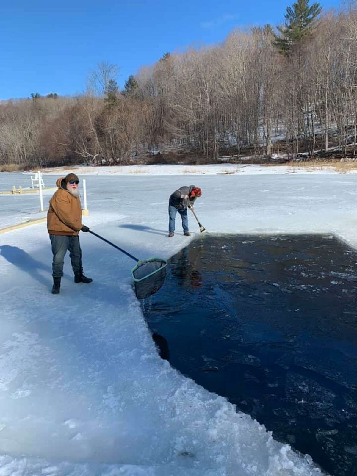 """Teams of employees from agencies and companies around Torrington participated in a """"penguin plunge"""" March 6 to raise money for Kids of Summer, a not-for-profit that provides money for camp scholarships and activities. Above, members of Hillview Property Maintenance cut and clear the ice for the plunge."""
