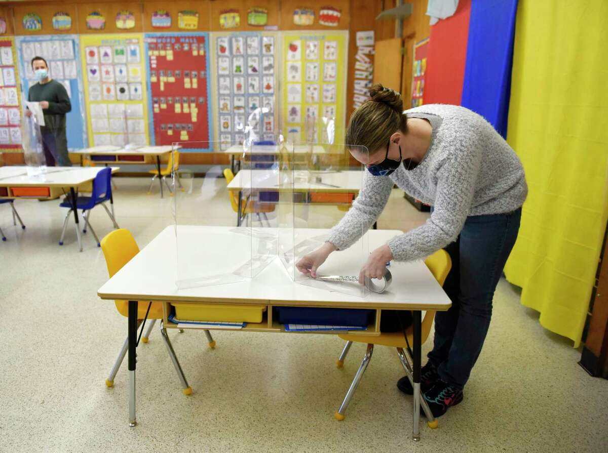 Kindergarten teacher Jaime Michaels sets up her classroom with COVID-19 precautions in place as students prepare to return five-days-a-week at Northeast Elementary School in Stamford, Conn. on Monday, March 8, 2021. For the first time in about a year, elementary students will return to full-time in-person learning starting Wednesday.
