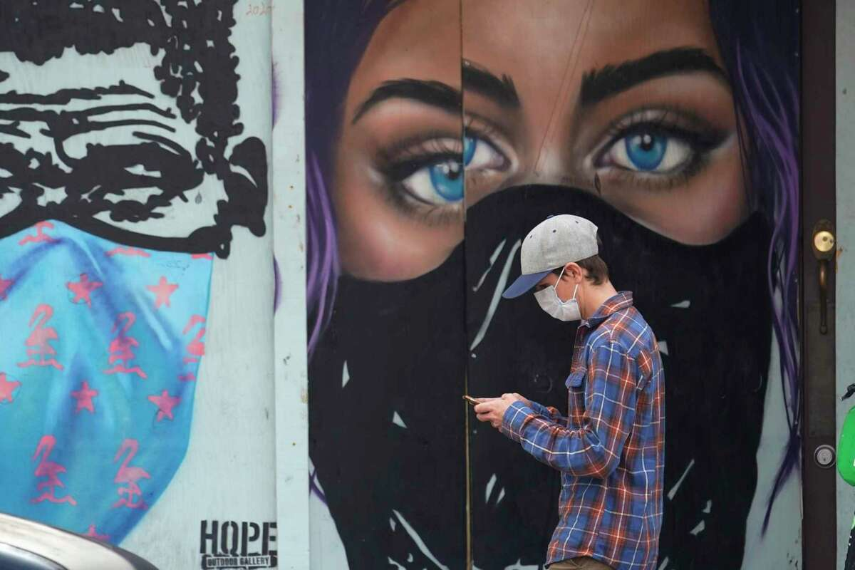 A pedestrian wearing a mask to protect against the spread on COVID-19 passes murals painted on a boarded-up business in downtown Austin, Texas, Tuesday, March 9, 2021. Texas Gov. Greg Abbot's mask mandate for the state ends Wednesday. (AP Photo/Eric Gay)