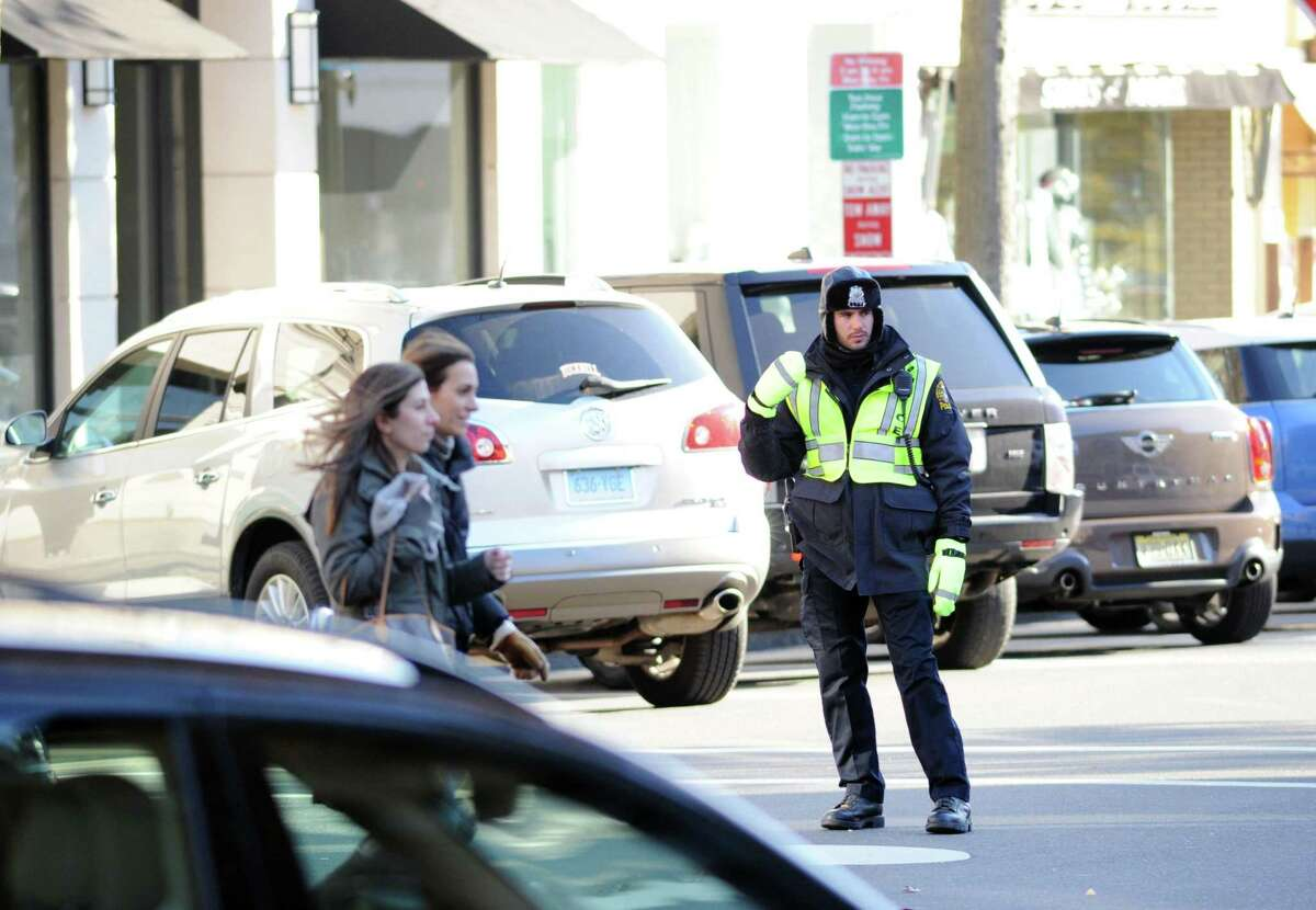 A Greenwich Police Officer directs traffic on Greenwich Avenue in Greenwich, Conn., Friday afternoon, Nov. 21, 2014.