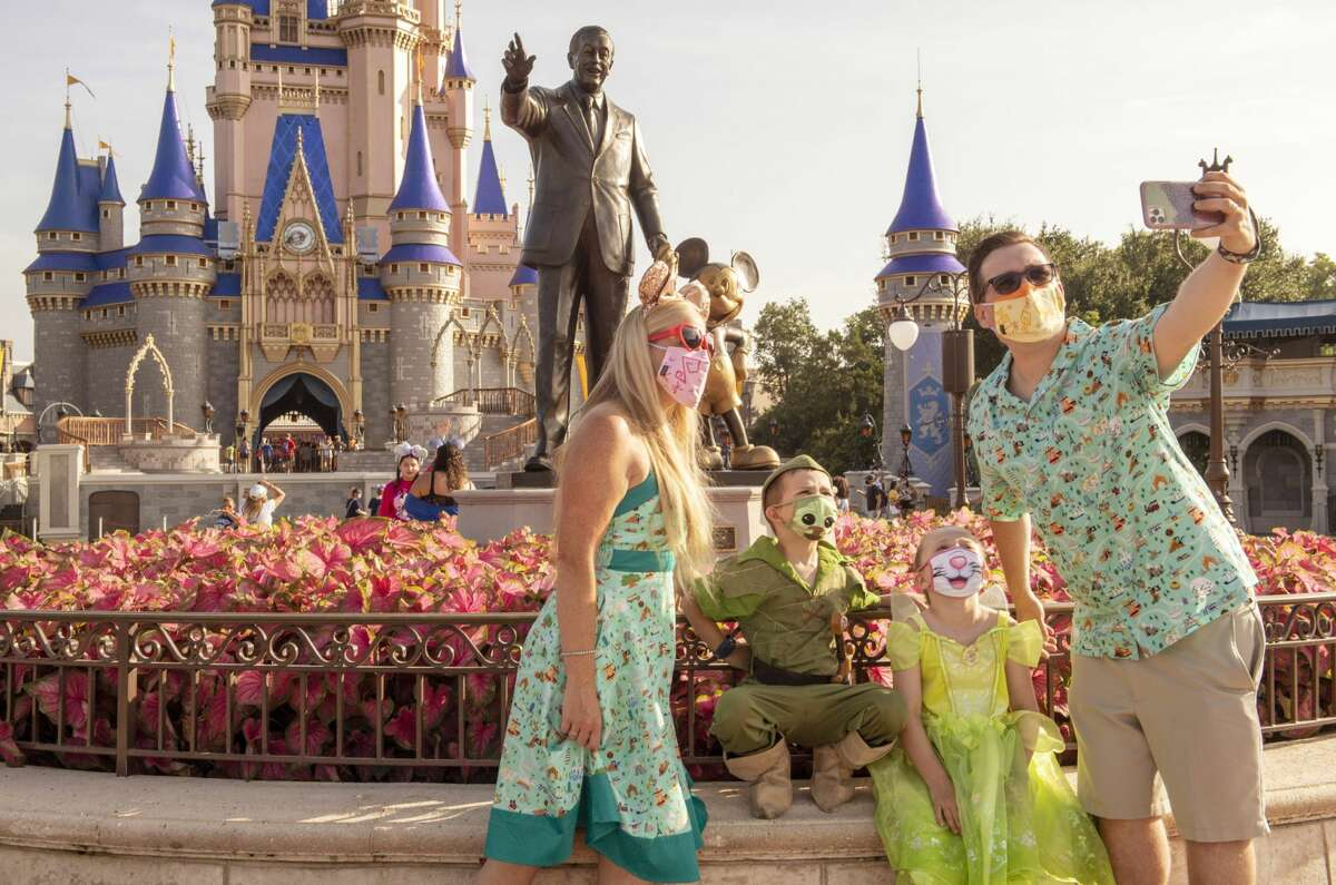 Guests stop to take a selfie at Magic Kingdom Park at Walt Disney World Resort on July 11, 2020, the day the park reopened.