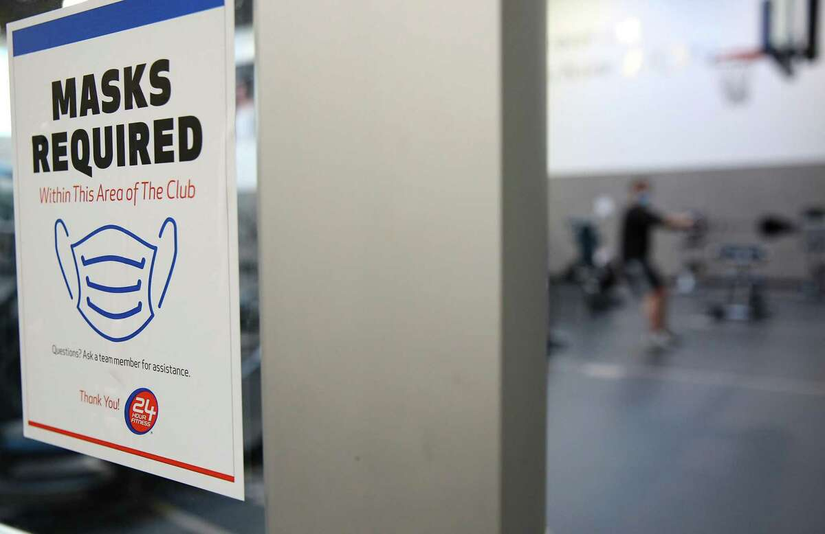 """A sign outside a small gym inside 24 Hour Fitness in Houston on Tuesday, March 9, 2021. As the statewide mask mandate lifts tomorrow, 24 Hour Fitness will have a """"gym within a gym"""", for those who want to workout with masks."""