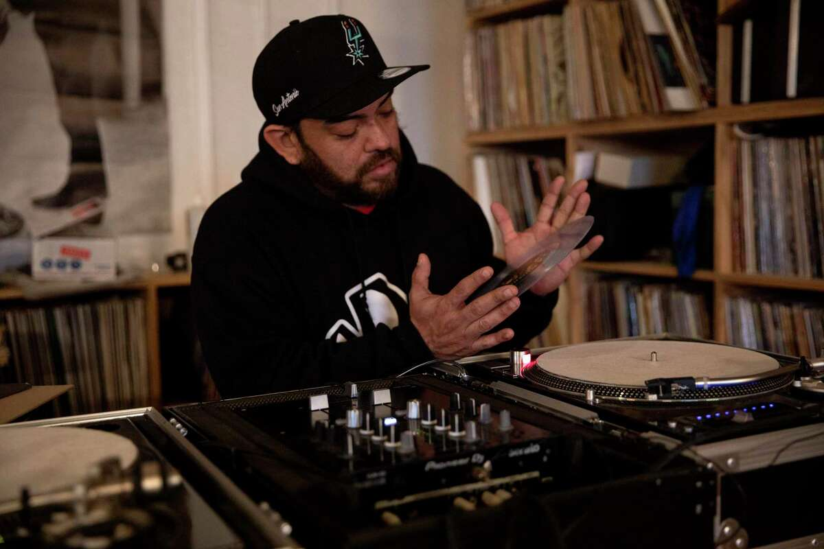 George Mendoza, owner of Friends of Sound Records, plays a record at his store.