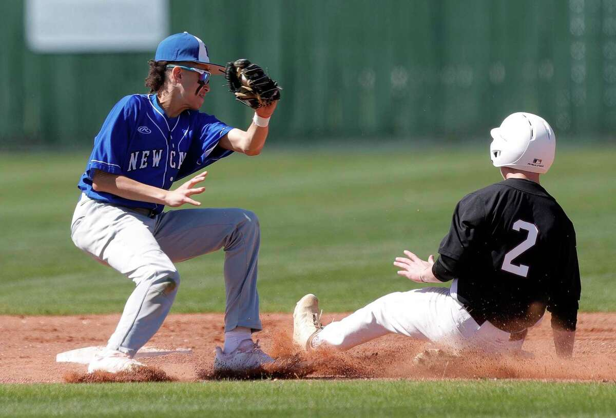 FILE - New Caney shortstop Kendall Dove (19) tries to apply a tag to Anthony Rivenbark #2 of Waller during the second inning of a high school baseball game at New Caney High School, Friday, March 6, 2020, in New Caney.
